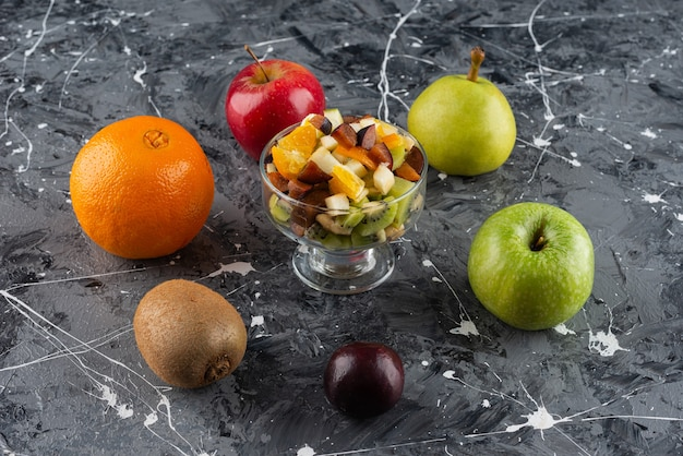 Glass bowl of sliced mixed salad with whole fresh fruits placed on a marble table.