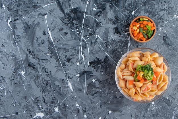 Ciotola di vetro di gustosa pasta di conchiglie con insalata fresca su superficie di marmo.