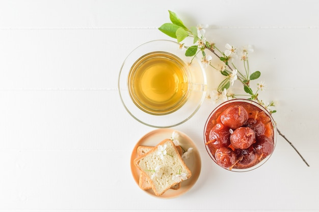 Glass bowl of whole apple jam and jasmine tea on a wooden table. homemade sweets according to old recipes. flat lay.