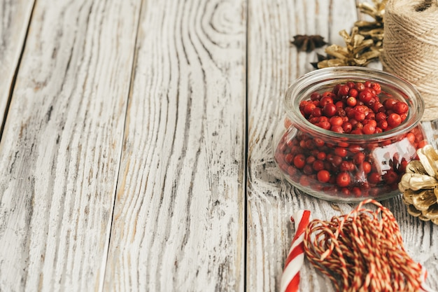 Glass bowl with cranberries on table close up