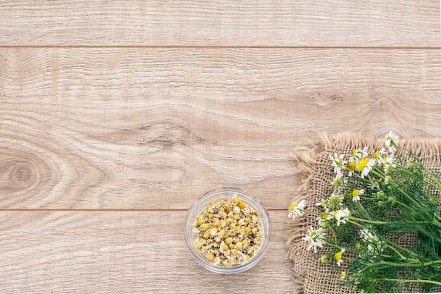 木の板にマトリカリアカモミールのドライフラワーと新鮮なカモミールの花が入ったガラスのボウル。コピースペースのある上面図。
