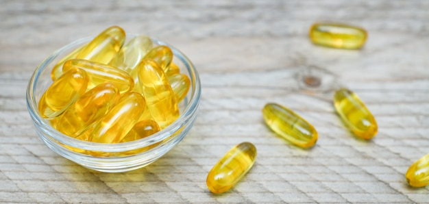 Glass bowl with fish oil capsules on wooden wall