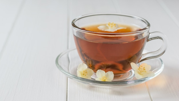 Glass bowl with herbal tea with jasmine flowers on a white wooden table.
