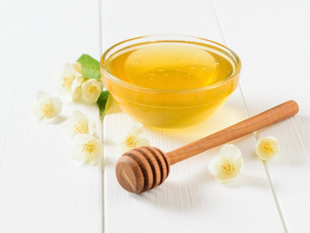 Glass bowl with honey and jasmine flowers on white wooden table.