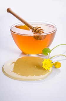 Glass bowl with honey and yellow flowers