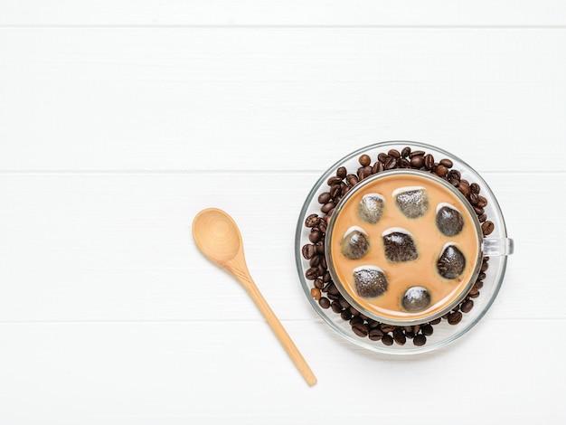 アイスコーヒーと白い木製のテーブルの上のコーヒー豆のガラスのボウル。さわやかで爽やかなコーヒー豆と牛乳のドリンク。上からの眺め。フラット横たわっていた。