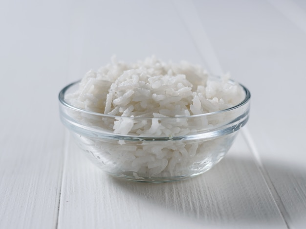 Glass bowl with long grain rice on white wooden table.