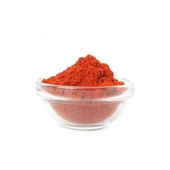 白で隔離される赤唐辛子粉末のガラスのボウル