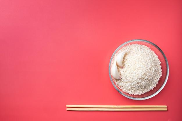 분홍색 배경에 쌀 마늘과 젓가락이 있는 유리 그릇