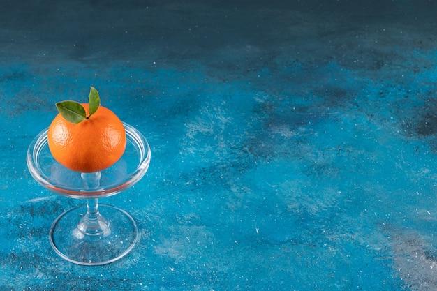 Ciotola di vetro con arancia succosa matura sul tavolo blu.