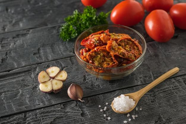 Стеклянная миска с жареными помидорами на поверхности свежего на деревянном столе