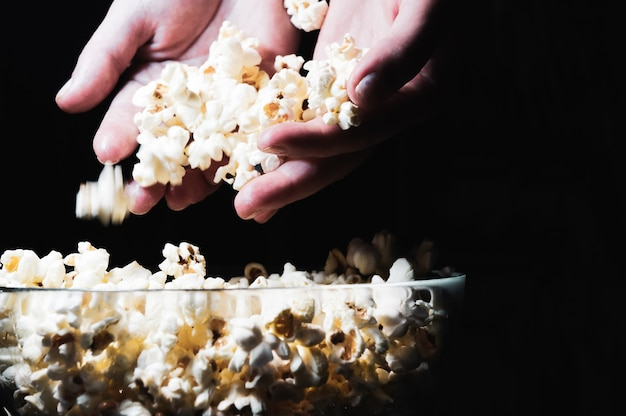 Glass bowl with salted popcorn on black for watching a movie