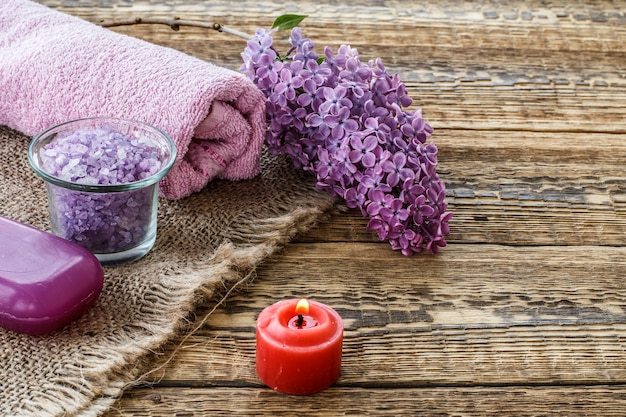 Glass bowl with sea salt, soap, burning candle, lilac flowers and towel for bathroom procedures on old wooden boards. spa products and accessories. top view.