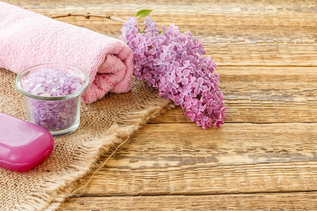 Glass bowl with sea salt, soap, lilac flowers and towel for bathroom procedures on wooden boards. spa products and accessories. top view.