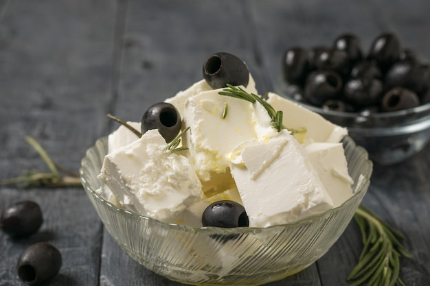 Glass bowl with slices of feta cheese and olives on a wooden table. natural cheese made from sheep's milk.