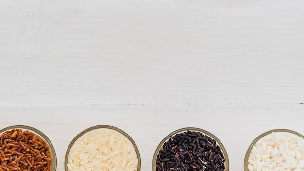 배경의 하단에 배열 된 쌀의 다양한 유리 그릇
