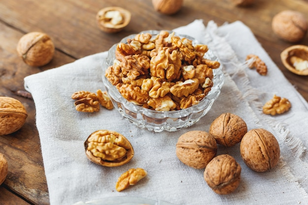 Glass bowl with walnuts on rustic homespun napkin