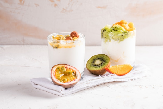 Glass bowl with yogurt and sliced fruits on white napkin