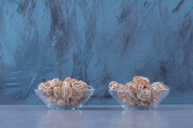 Ciotole di vetro piene di cereali sani sul tavolo grigio.