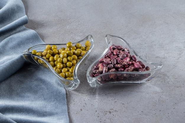 石の背景に生豆とグリーンピースでいっぱいのガラスのボウル。