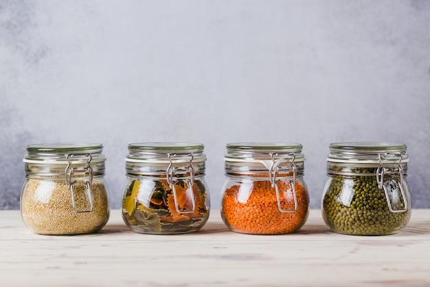 Стеклянные коробки и бутылки с киноа, чечевица, пюре, макароны организованы дома простой стильный хранения без пластика