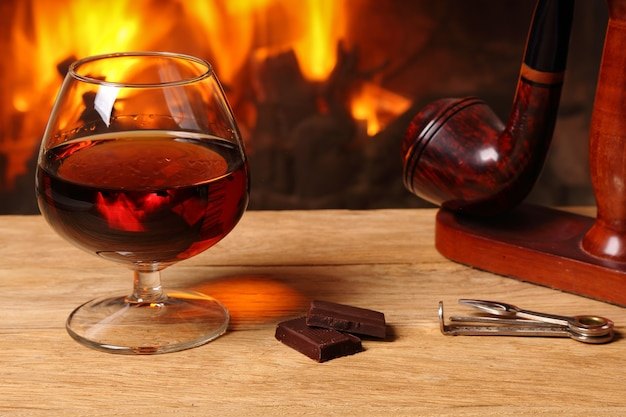 A glass of brandy, chocolate and tobacco pipe on oak table on the background of a burning fireplace