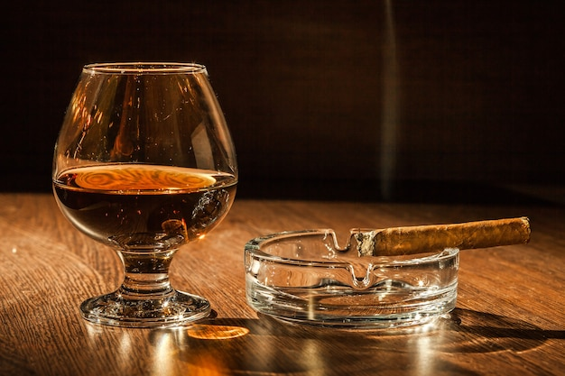 A glass of brandy and a cigar on the wooden table.