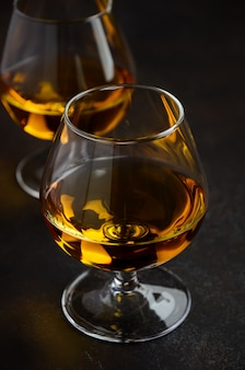 Glass of brandy or cognac on the old rusty background.