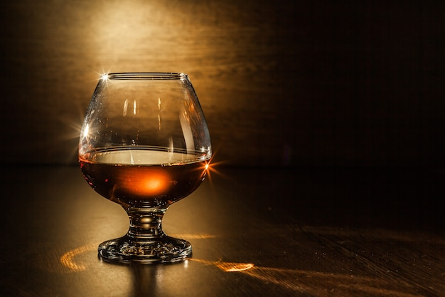 A glass of brandy on the wooden table.