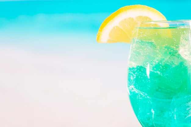 Glass of bright blue drink with lime