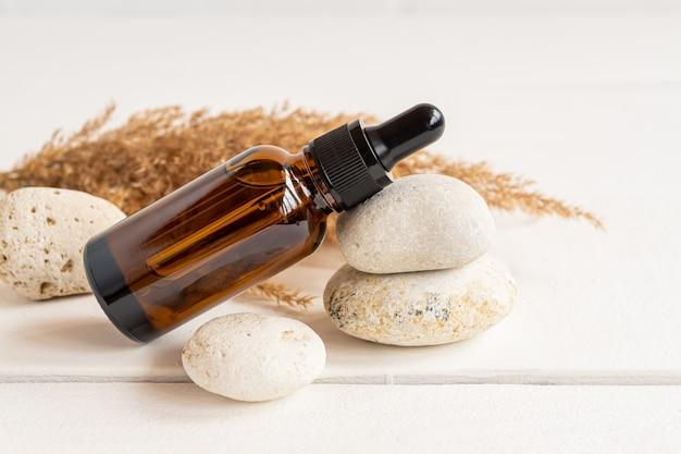 スキンケア用のピペット付きの血清のガラス茶色のボトルは石の上にあります。有機成分を含む化粧品。健康と美容の概念。ミニマリズム、コピースペース。