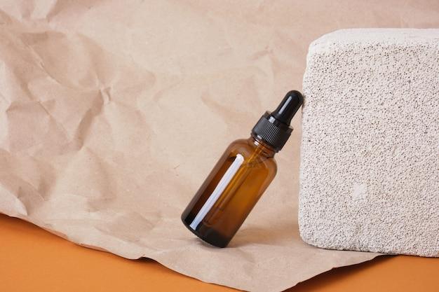 Стеклянная коричневая бутылка с капельницей для косметики на бетонном блоке