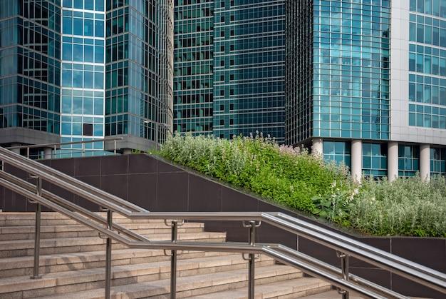 ビジネス都市地区のガラスの建物、階段、緑の植物