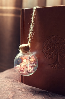 Glass bulb with dried flowers inside on a book cover