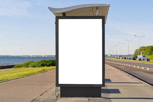 흰색 광고 공간이있는 바다 옆 유리 버스 정류장