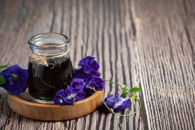 Glass of butterfly pea flower tea put on wooden tray