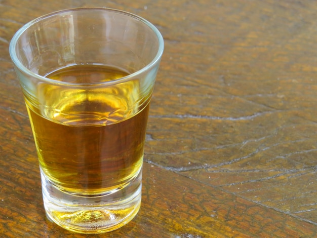 Glass of cachaca on wooden table
