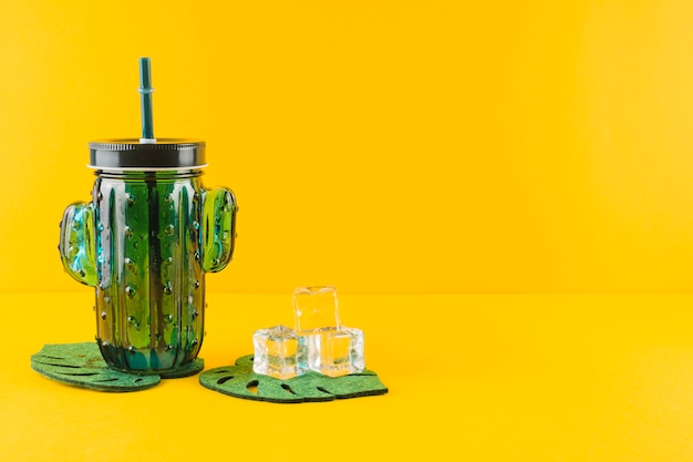 Glass cactus juice jar and crystal ice cubes on leaves coasters against yellow backdrop