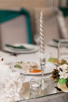 銀のろうそくと他の装飾品とガラスの燭台は机の上にあります