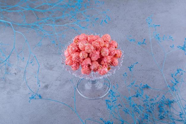Стеклянный держатель для конфет, наполненный конфетами из попкорна, рядом с декоративными синими ветками на мраморной поверхности