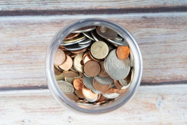 Glass canister full of old coins.