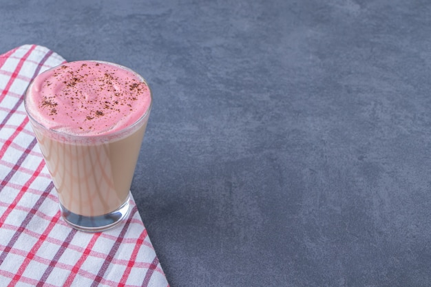 Un bicchiere di cappuccino su un canovaccio, sullo sfondo di marmo. foto di alta qualità