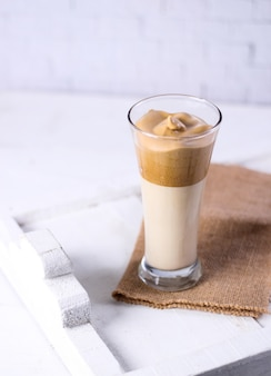 Glass of caramel smoothie on a brown piece of clothing next to a white surface
