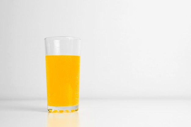 Glass of carbonated juice standing on table indoors. light background, copy space