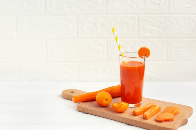Glass of carrot juice and fresh carrot on cutting board