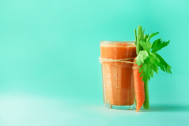 Glass of carrot juice with carrots, celery on blue background.