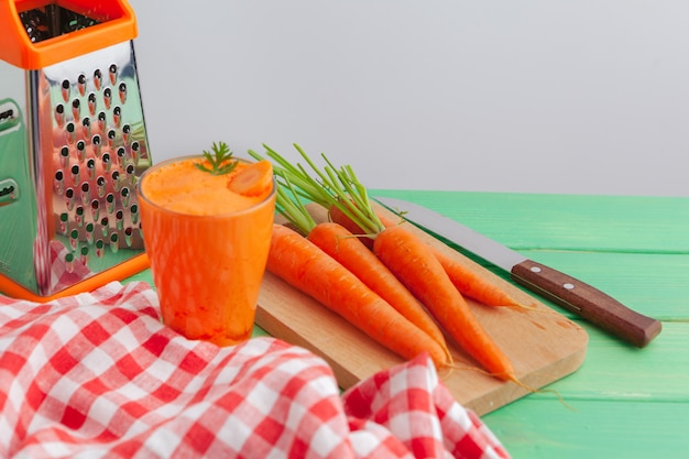 Glass of carrot juice with vegetables on table