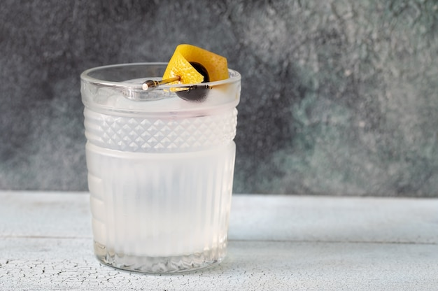 Glass of casino cocktail garnished with a lemon zest and a maraschino cherry