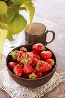 잘 익은 fress 딸기와 저녁 식사 테이블에 어두운 유리 유리 세라믹 그릇.