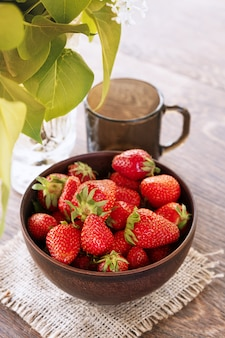 Glass ceramic bowl with ripe fress strawberries and dark glass on a dinner table.